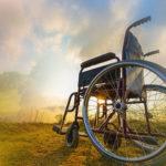 Pusty wózek inwalidzki na tle pejzarzu z zachodzącym słońcem.